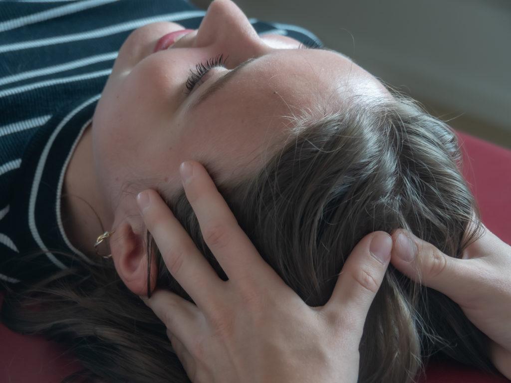 Osteopathin Nora Rabe behandelt den Kopf einer sich in Rückenlage befindenden Patientin. Beide Hände umfassen den Kopf von links und rechts.